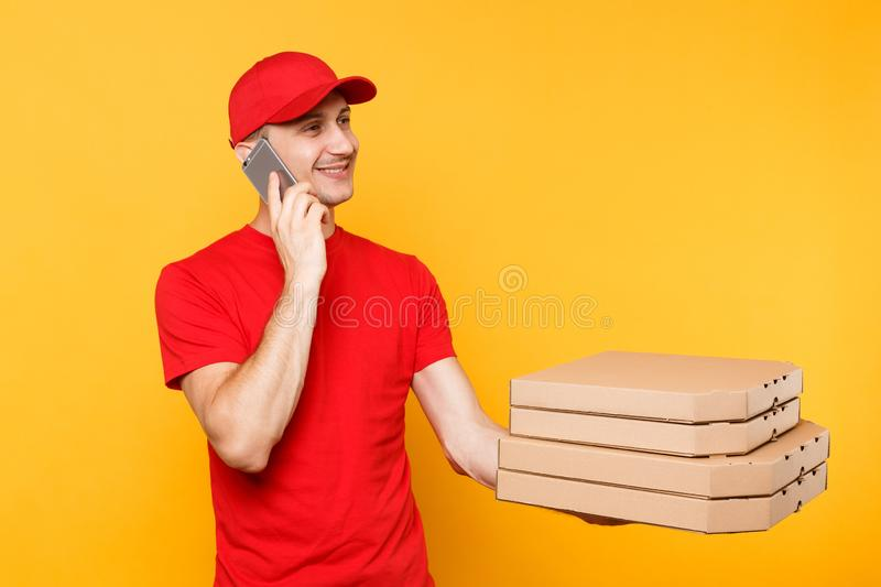 Delivery man in red cap t-shirt giving food order italian pizza in blank empty flatbox boxes on yellow background. Male. Employee pizzaman courier talking on royalty free stock images