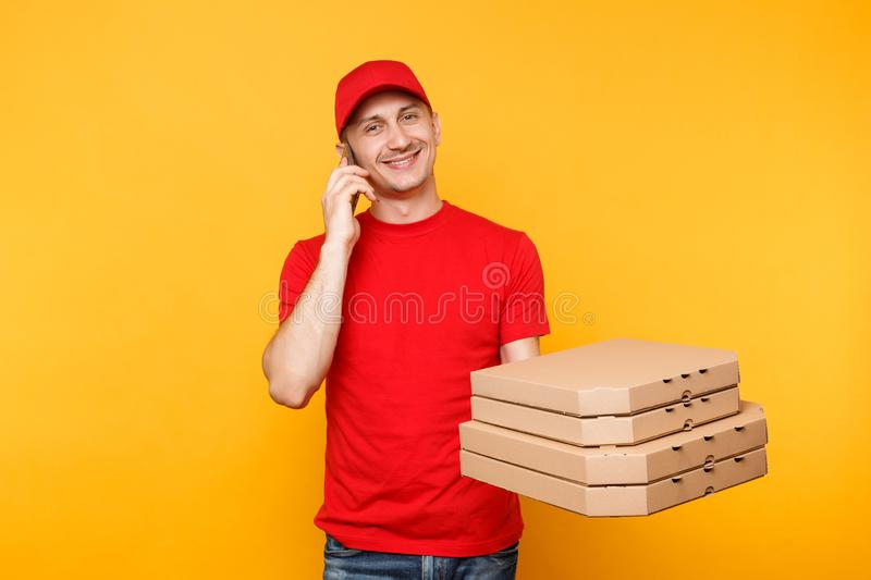Delivery man in red cap t-shirt giving food order italian pizza in blank empty flatbox boxes on yellow background. Male. Employee pizzaman courier talking on stock image