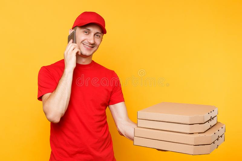 Delivery man in red cap t-shirt giving food order italian pizza in blank empty flatbox boxes on yellow background. Male. Employee pizzaman courier talking on royalty free stock photography