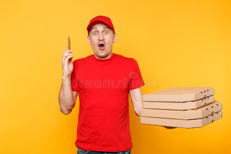 Delivery man in red cap t-shirt giving food order italian pizza in blank empty flatbox boxes on yellow background. Male. Employee pizzaman courier talking on stock photos