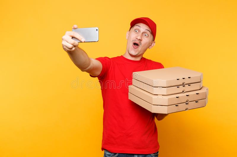 Delivery man in red cap t-shirt giving food order italian pizza in empty flatbox boxes on yellow background. Male. Employee pizzaman courier doing taking selfie stock photo