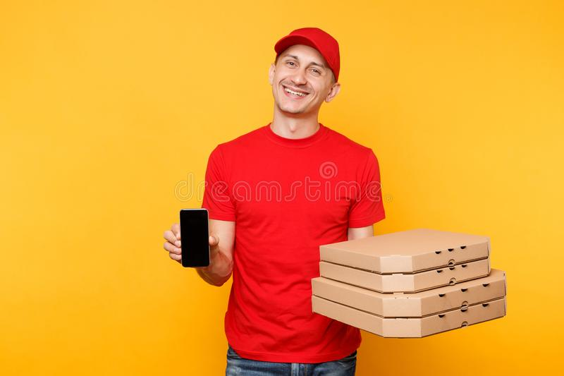 Delivery man in red cap t-shirt giving food order italian pizza in flatbox boxes on yellow background. Male employee. Pizzaman courier hold mobile phone with stock photos