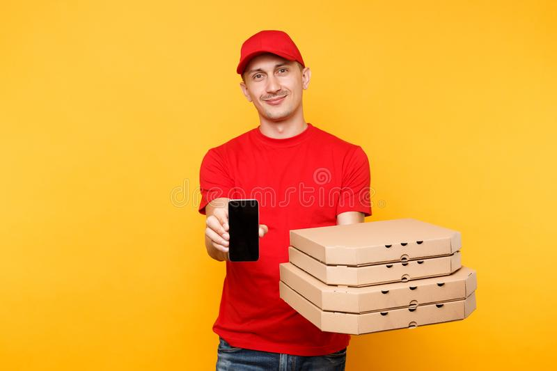 Delivery man in red cap t-shirt giving food order italian pizza in flatbox boxes on yellow background. Male employee. Pizzaman courier hold mobile phone with stock image