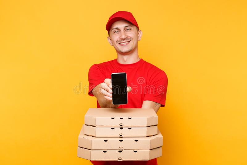Delivery man in red cap t-shirt giving food order italian pizza in flatbox boxes on yellow background. Male employee. Pizzaman courier hold mobile phone with stock photography