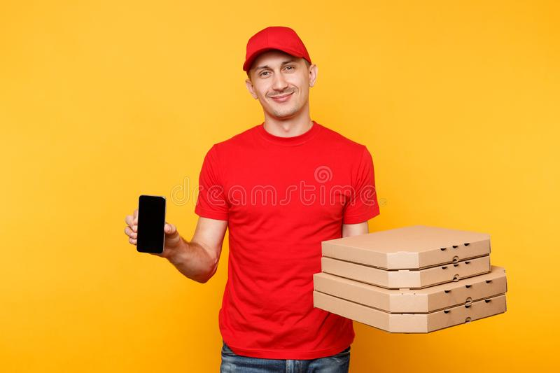 Delivery man in red cap t-shirt giving food order italian pizza in flatbox boxes on yellow background. Male employee. Pizzaman courier hold mobile phone with royalty free stock images