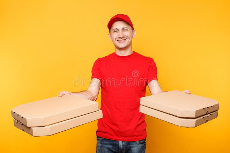 Delivery man in red cap, t-shirt giving food order pizza boxes isolated on yellow background. Male employee pizzaman or. Courier in uniform holding italian royalty free stock images