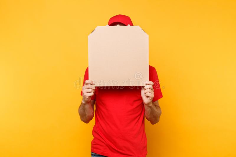 Delivery man in red cap, t-shirt giving food order pizza boxes isolated on yellow background. Male employee pizzaman. Courier holding pizza in empty blank royalty free stock images