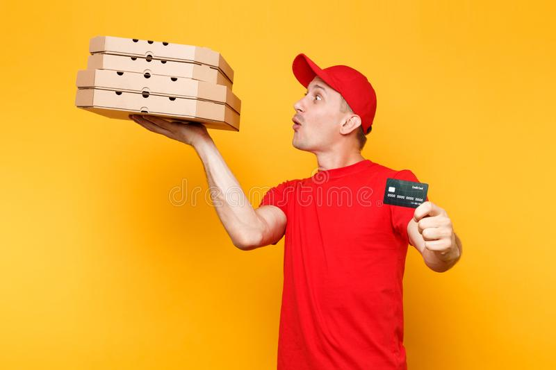 Delivery man in red cap t-shirt giving food order pizza boxes isolated on yellow background. Male employee pizzaman. Courier holding italian pizza in cardboard royalty free stock photos