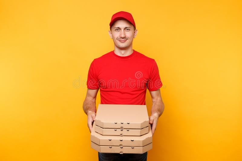 Delivery man in red cap, t-shirt giving food order pizza boxes isolated on yellow background. Male employee pizzaman or. Courier in uniform holding italian royalty free stock photography