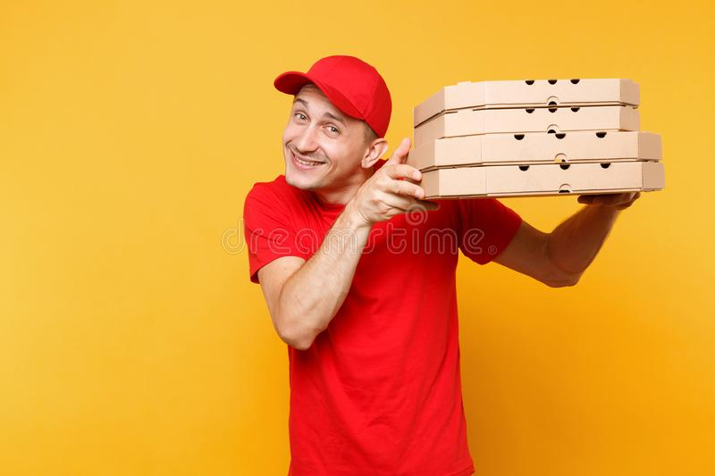 Delivery man in red cap, t-shirt giving food order pizza boxes isolated on yellow background. Male employee pizzaman or. Courier in uniform holding italian royalty free stock photos
