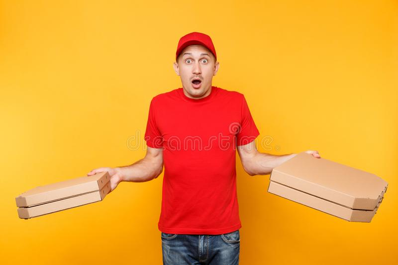 Delivery man in red cap, t-shirt giving food order pizza boxes isolated on yellow background. Male employee pizzaman or. Courier in uniform holding italian royalty free stock image