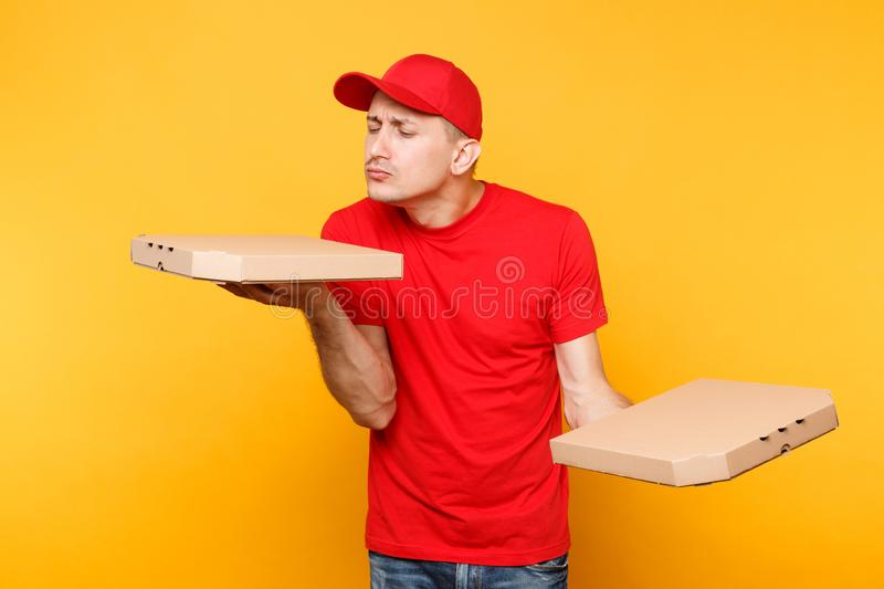 Delivery man in red cap, t-shirt giving food order pizza boxes isolated on yellow background. Male employee pizzaman or. Courier in uniform holding italian stock photos