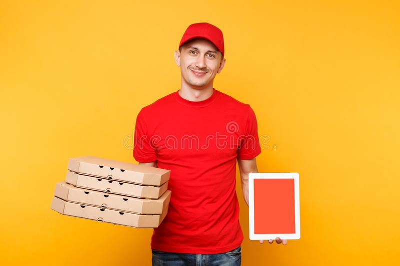 Delivery man in red cap t-shirt giving food order pizza in flatbox boxes on yellow background. Male employee pizzaman. Courier hold tablet pc computer with royalty free stock photos