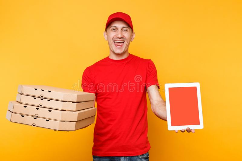 Delivery man in red cap t-shirt giving food order pizza in flatbox boxes on yellow background. Male employee pizzaman. Courier hold tablet pc computer with royalty free stock images