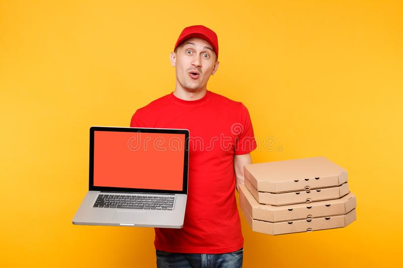 Delivery man in red cap t-shirt giving food order pizza in flatbox boxes on yellow background. Male employee pizzaman. Courier hold laptop pc computer with royalty free stock photo
