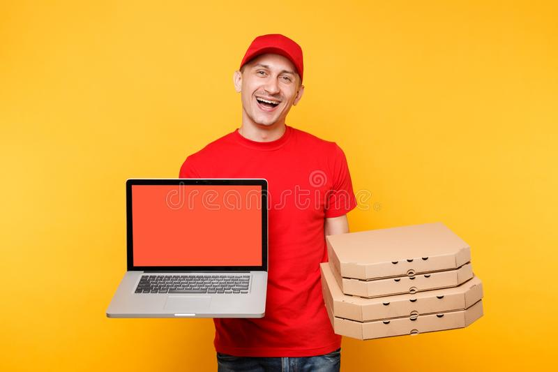 Delivery man in red cap t-shirt giving food order pizza in flatbox boxes on yellow background. Male employee pizzaman. Courier hold laptop pc computer with royalty free stock photography