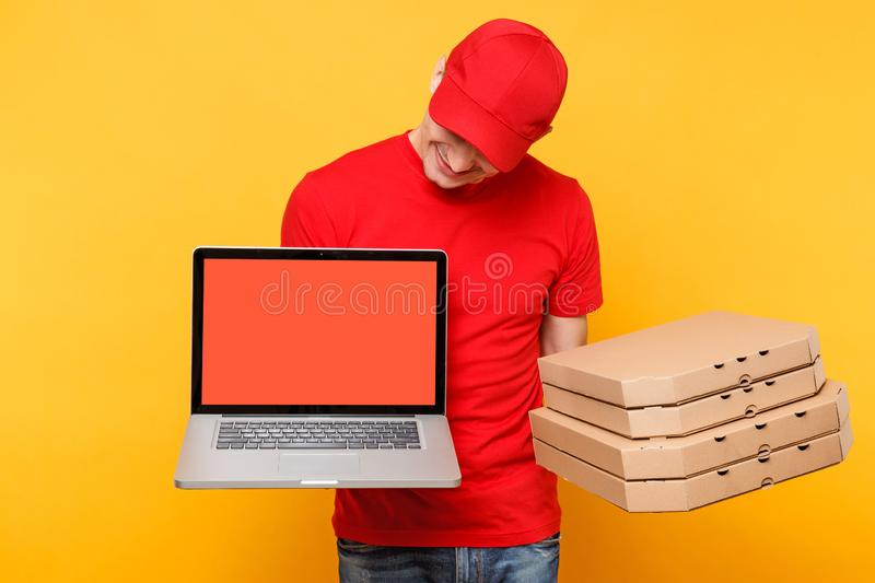 Delivery man in red cap t-shirt giving food order pizza in flatbox boxes on yellow background. Male employee pizzaman. Courier hold laptop pc computer with royalty free stock photos