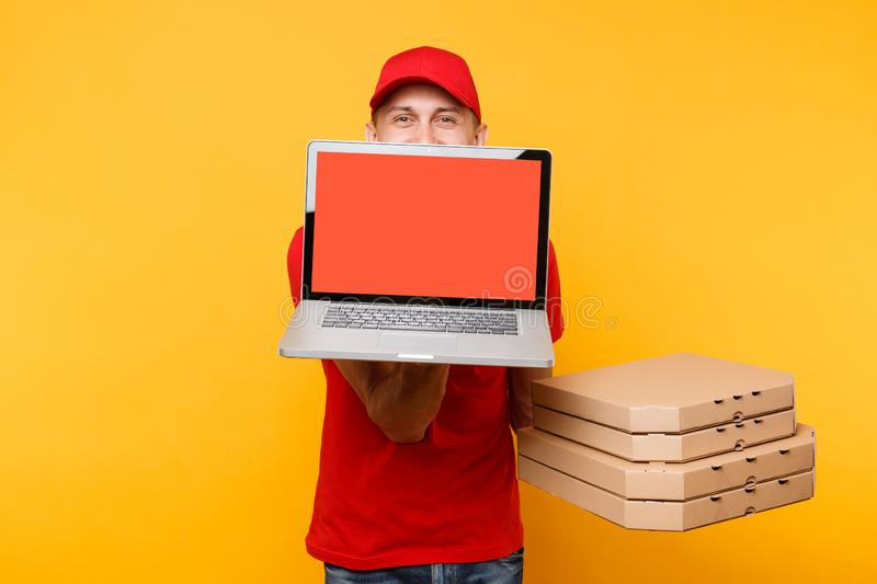 Delivery man in red cap t-shirt giving food order pizza in flatbox boxes on yellow background. Male employee pizzaman. Courier hold laptop pc computer with royalty free stock image