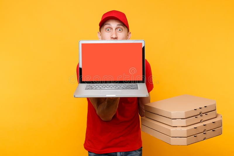 Delivery man in red cap t-shirt giving food order pizza in flatbox boxes on yellow background. Male employee pizzaman. Courier hold laptop pc computer with stock photo
