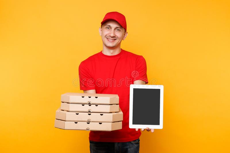 Delivery man in red cap t-shirt giving food order pizza in flatbox boxes on yellow background. Male employee pizzaman. Courier hold tablet pc computer with royalty free stock photo