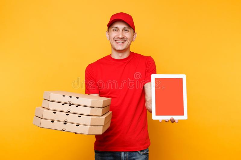 Delivery man in red cap t-shirt giving food order pizza in flatbox boxes on yellow background. Male employee pizzaman. Courier hold tablet pc computer with stock images