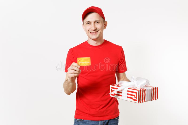 Delivery man in red uniform isolated on white background. Male in cap, t-shirt, jeans working as courier or dealer with. Credit card, red striped gift box with royalty free stock photography