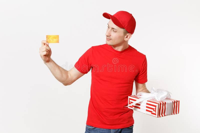 Delivery man in red uniform isolated on white background. Male in cap, t-shirt, jeans working as courier or dealer with. Credit card, red striped gift box with royalty free stock images