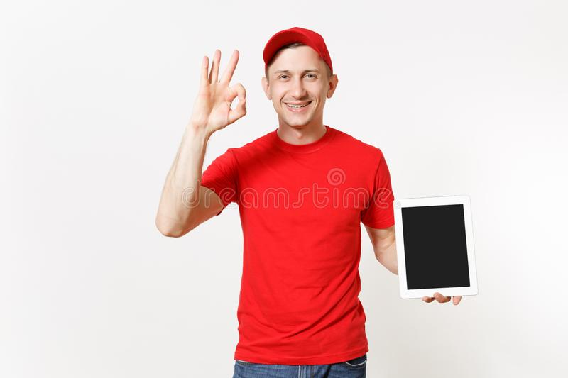 Delivery man in red uniform isolated on white background. Male in cap, t-shirt, jeans working as courier or dealer. Holding tablet pc computer with blank empty stock image