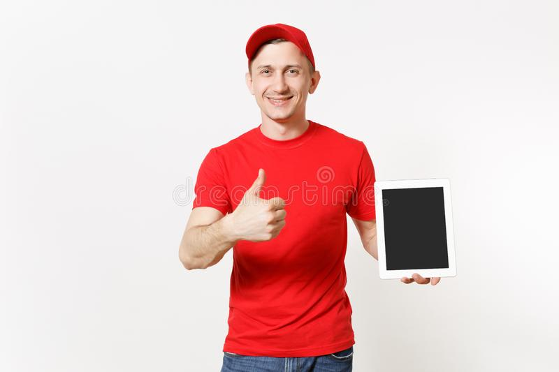 Delivery man in red uniform isolated on white background. Male in cap, t-shirt, jeans working as courier or dealer. Holding tablet pc computer with blank empty royalty free stock image