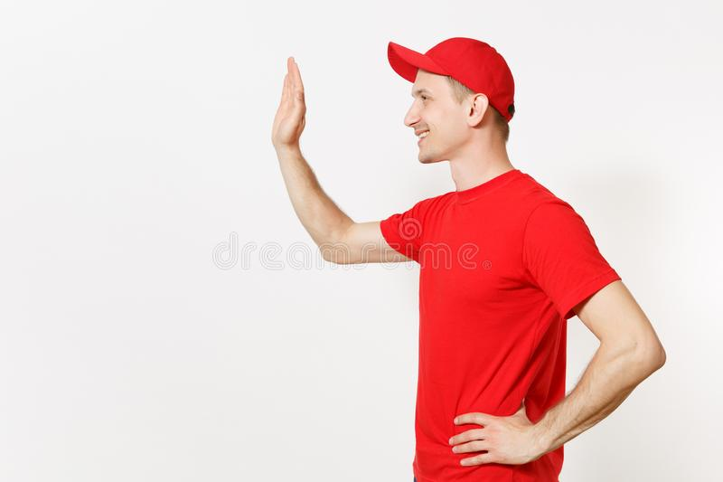 Delivery man in red uniform isolated on white background. Male in cap, t-shirt working as courier or dealer, waving and. Greeting with hand as notices someone royalty free stock images