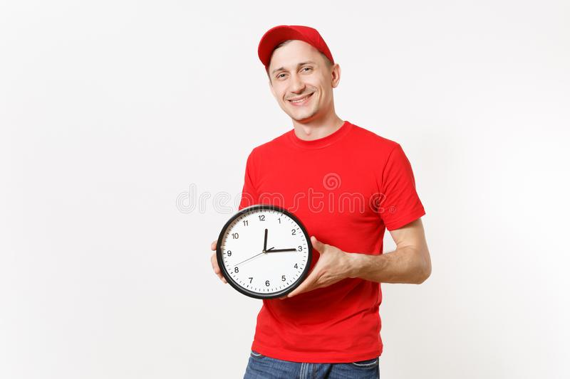 Delivery man in red uniform isolated on white background. Professional male in cap, t-shirt, jeans working as courier or. Dealer, holding round clock, showing stock photos