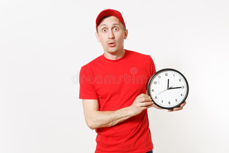 Delivery man in red uniform isolated on white background. Professional male in cap, t-shirt, jeans working as courier or. Dealer, holding round clock, showing royalty free stock image