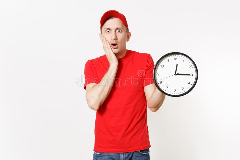 Delivery man in red uniform isolated on white background. Professional male in cap, t-shirt, jeans working as courier or. Dealer, holding round clock, showing stock photography