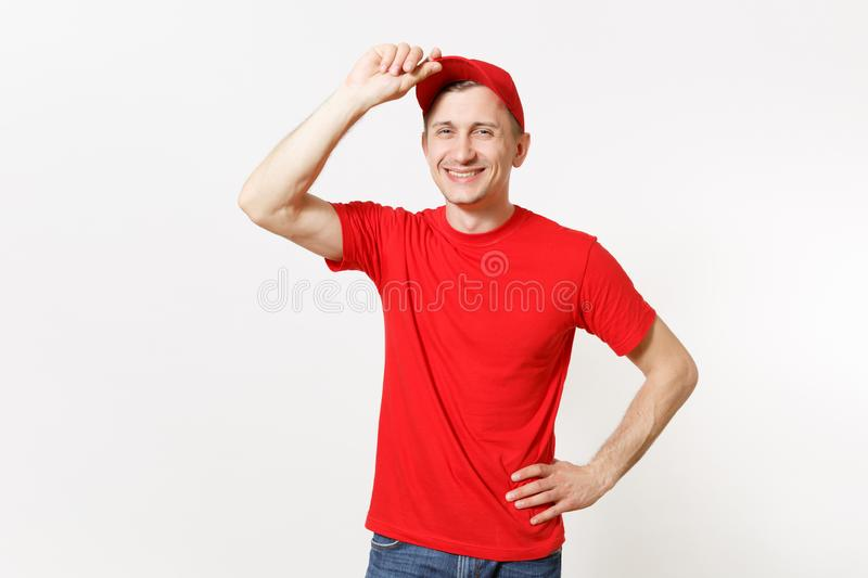Delivery man in red uniform isolated on white background. Professional smiling caucasian male in cap, t-shirt working as. Courier or dealer, put his hand on hat royalty free stock photo