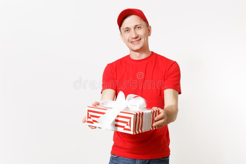 Delivery man in red uniform isolated on white background. Smiling male in cap, t-shirt, jeans working as courier or. Dealer, holding red striped gift box with stock photo