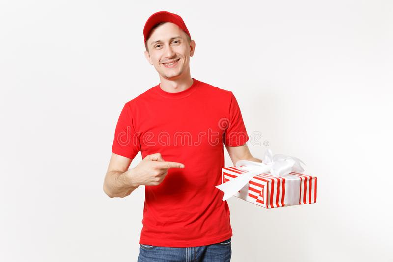Delivery man in red uniform isolated on white background. Smiling male in cap, t-shirt, jeans working as courier or. Dealer, holding red striped gift box with royalty free stock photo