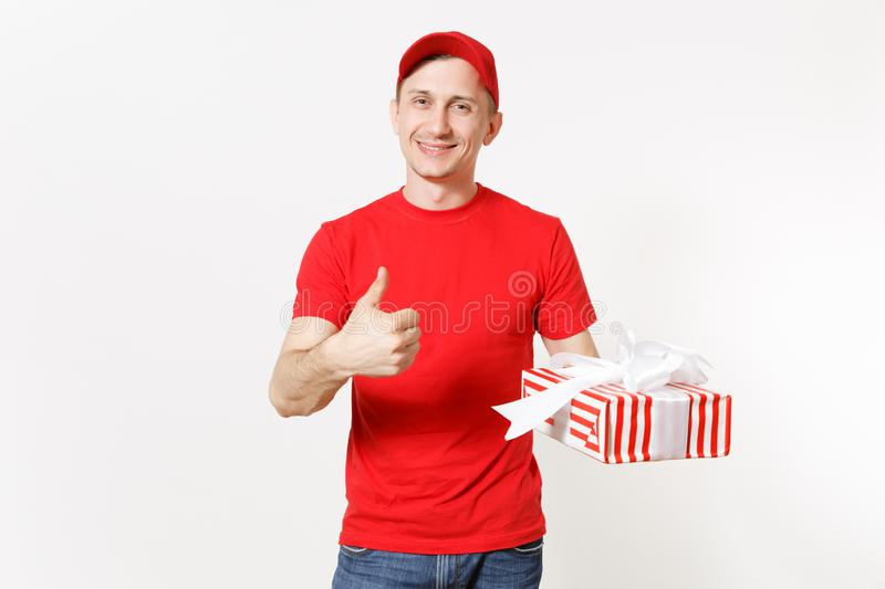 Delivery man in red uniform isolated on white background. Smiling male in cap, t-shirt, jeans working as courier or. Dealer, holding red striped gift box with stock images