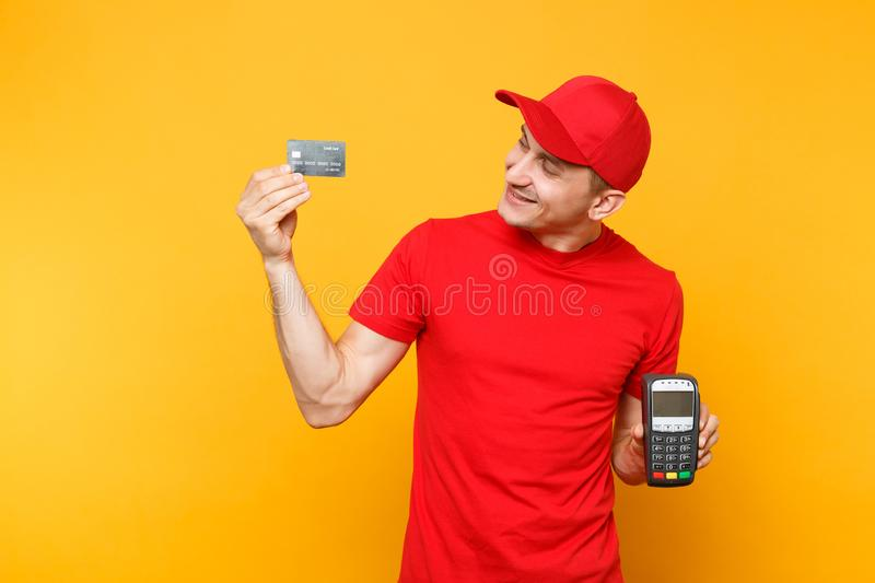 Delivery man in red uniform isolated on yellow background. Male employee in cap, t-shirt courier holding wireless modern. Bank payment terminal to process and royalty free stock photos