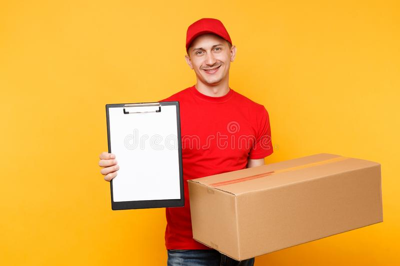 Delivery man in red uniform isolated on yellow background. Male employee courier in cap t-shirt hold pen clipboard with. Papers document, blank empty sheet royalty free stock photo