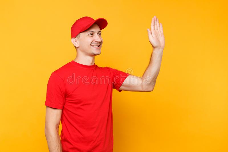 Delivery man in red uniform isolated on yellow background. Smiling male employee in cap, t-shirt courier dealer waving. And greeting with hand as notices stock photos