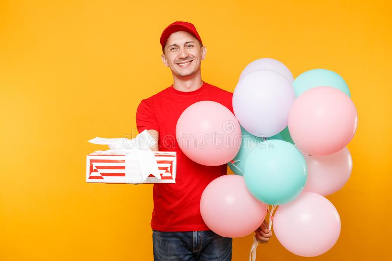 Delivery man in red uniform isolated on yellow orange background. Male employee in cap, t-shirt courier dealer holding. Bunch of colorful pastel air balloons stock photo