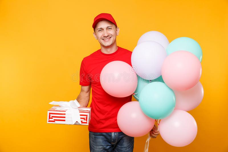Delivery man in red uniform isolated on yellow orange background. Male employee in cap, t-shirt courier dealer holding. Bunch of colorful pastel air balloons stock images