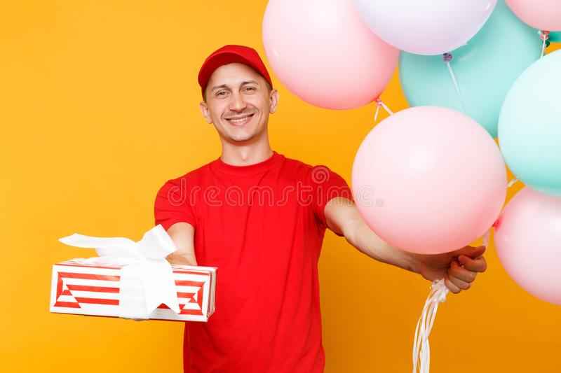 Delivery man in red uniform isolated on yellow orange background. Male employee in cap, t-shirt courier dealer holding. Bunch of colorful pastel air balloons royalty free stock image