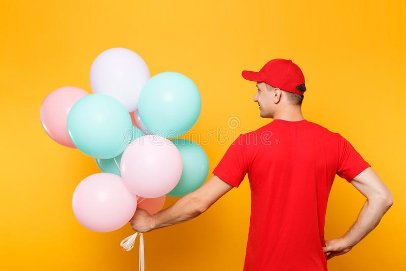 Delivery man in red uniform isolated on yellow orange background. Male employee in cap, t-shirt courier dealer holding. Delivery man in red uniform isolated on stock image