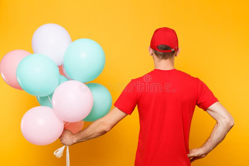 Delivery man in red uniform isolated on yellow orange background. Male employee in cap, t-shirt courier dealer holding. Delivery man in red uniform isolated on royalty free stock photos