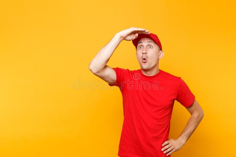 Delivery man in red uniform isolated on yellow orange background. Male employee in cap, t-shirt working courier dealer. Holding hand at forehead looking far stock photo