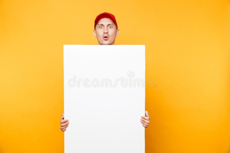 Delivery man in red uniform isolated on yellow orange background. Male employee courier in cap, t-shirt holding big. White empty blank billboard with copy space royalty free stock images