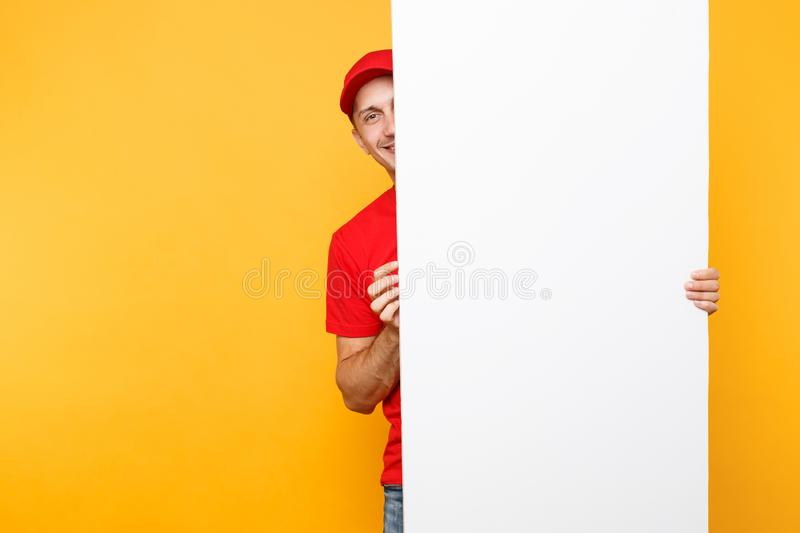 Delivery man in red uniform isolated on yellow orange background. Male employee courier in cap, t-shirt holding big. White empty blank billboard with copy space royalty free stock photo