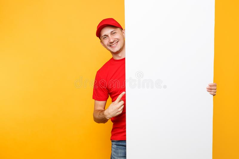 Delivery man in red uniform isolated on yellow orange background. Male employee courier in cap, t-shirt holding big. White empty blank billboard with copy space royalty free stock photography