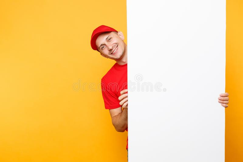 Delivery man in red uniform isolated on yellow orange background. Male employee courier in cap, t-shirt holding big. White empty blank billboard with copy space royalty free stock image